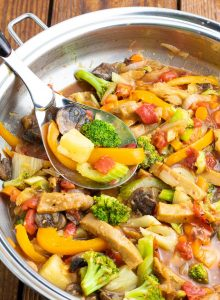 close up of sweet and sour vegan stir fry in wok with spoon