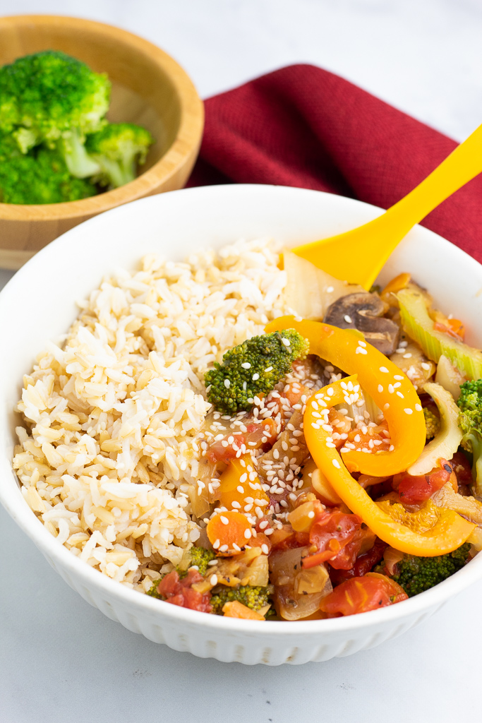 white bowl half filled with rice and other half stir fry
