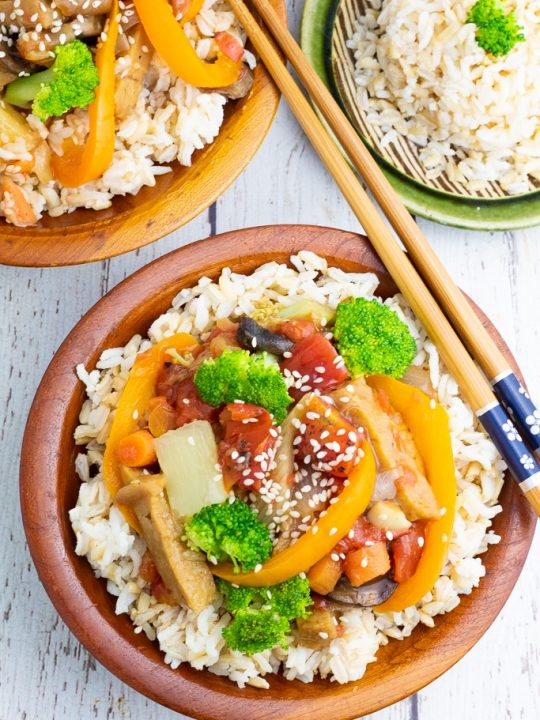 wooden bowl filled with rice and stir fry with chopsticks