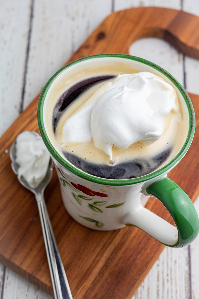 coffee in cup topped with vegan whipped cream