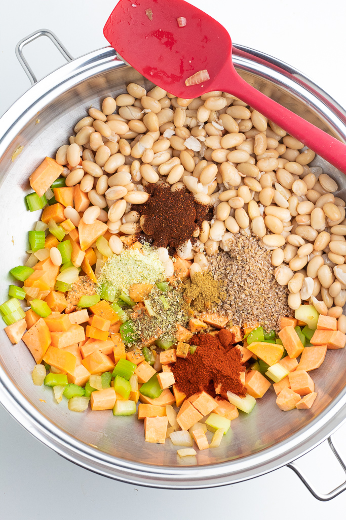 stainless pot filled with white beans, sweet potatoes, onions, garlic, celery, spices
