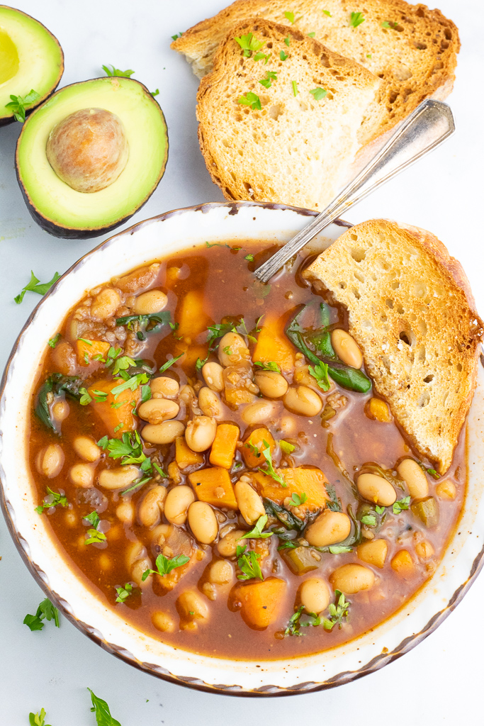 close up of bowl of white bean chili with avocado and crusty bread