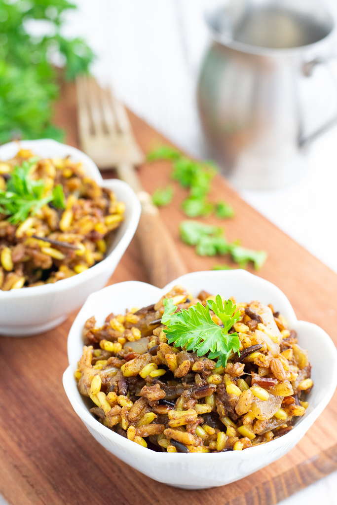 white flower bowl filled with seasoned wild rice topped with parsley