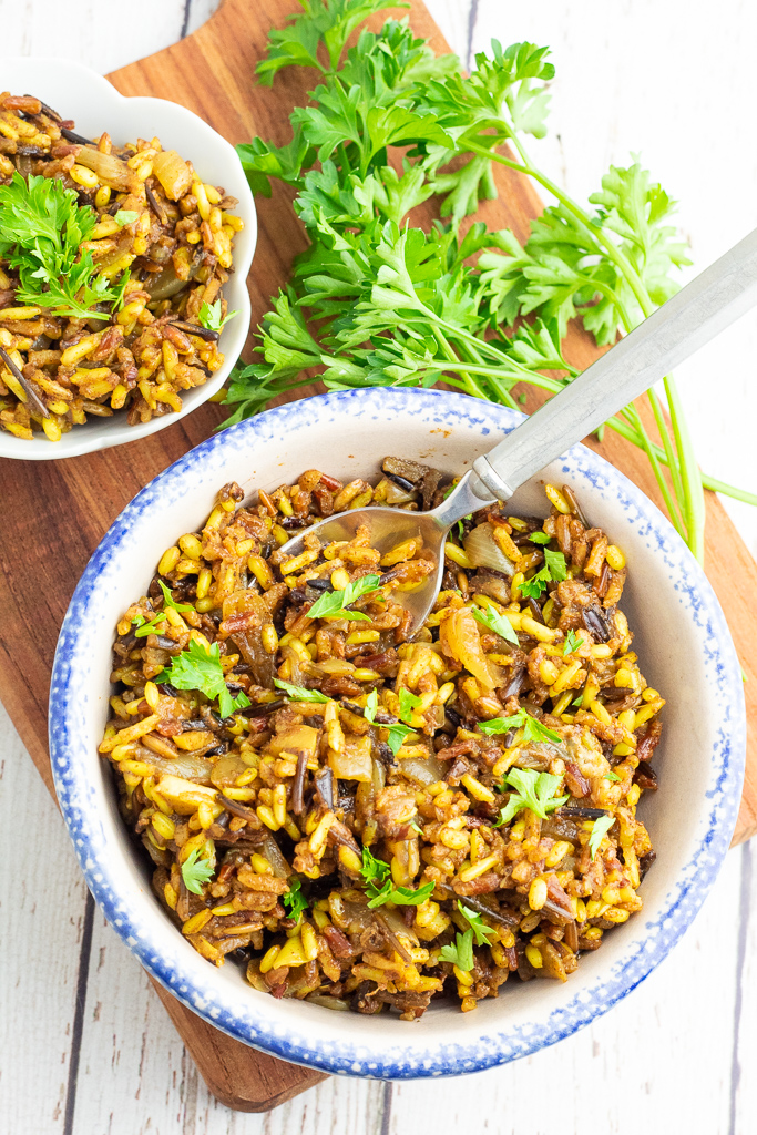 white and blue bowl filled with colorful wild rice with spoon and bunch of parsley