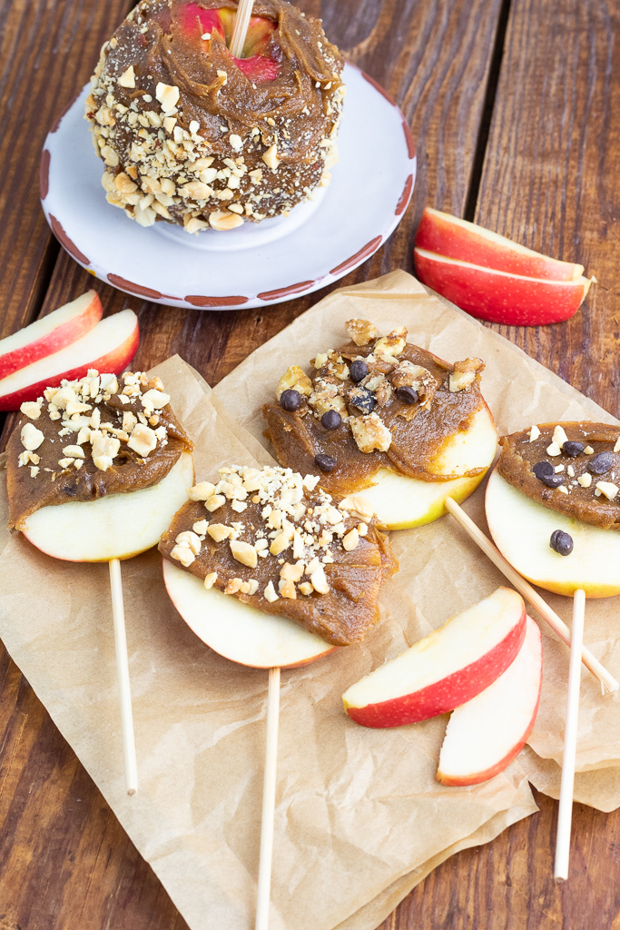 apple slices on sticks and dipped in vegan caramel and nuts